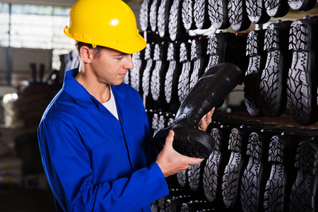 32755935 - factory worker looking at gumboots in a storeroom