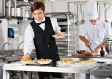 22348577 - waiter and chef working in commercial kitchen