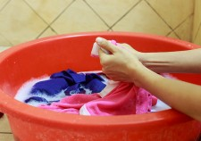 37448401 - two hands washing clothes in red tub
