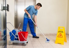 Happy Male Janitor With Cleaning Equipments Mopping Floor