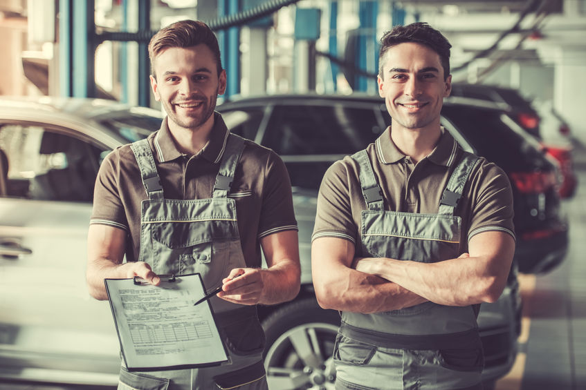 Handsome young auto mechanics in uniform are showing documents to fill and smiling while working in auto service