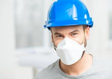 Portrait of a builder or repairman in protective helmet and facial mask indoors