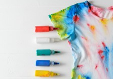 Tubes of paint for clothes and t-shirt in tie dye style on a white wooden table. White clothes painted by hand. Flat lay.
