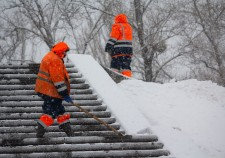 Kiev, Ukraine - January 18, 2018: Workers in public services in orange æèëåòàõ clean snow in heavy snow