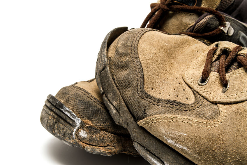 a close up, high resolution picture of a dirty and broken pair of brown shoes