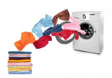 Washing machine and flying clothes on white background