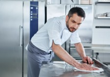 Bearded man prepares the surface for cooking in the kitchen. Cook carefully wipes the surface. Health and safety concept.