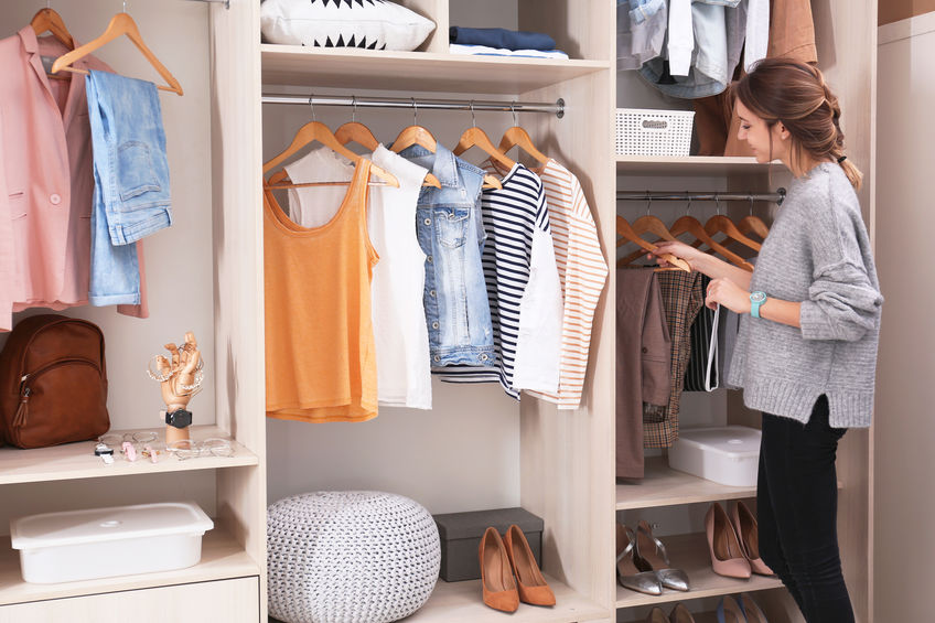 Woman choosing outfit from large wardrobe closet with stylish clothes, shoes and home stuff