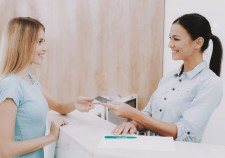Woman Receptionist. Business Card in Salon. Workplace in Beauty Salon. White Interior. White Reception Desk. Beauty Consept. Smiling Salon Employee. Customer Registration. Employee Talking Client.