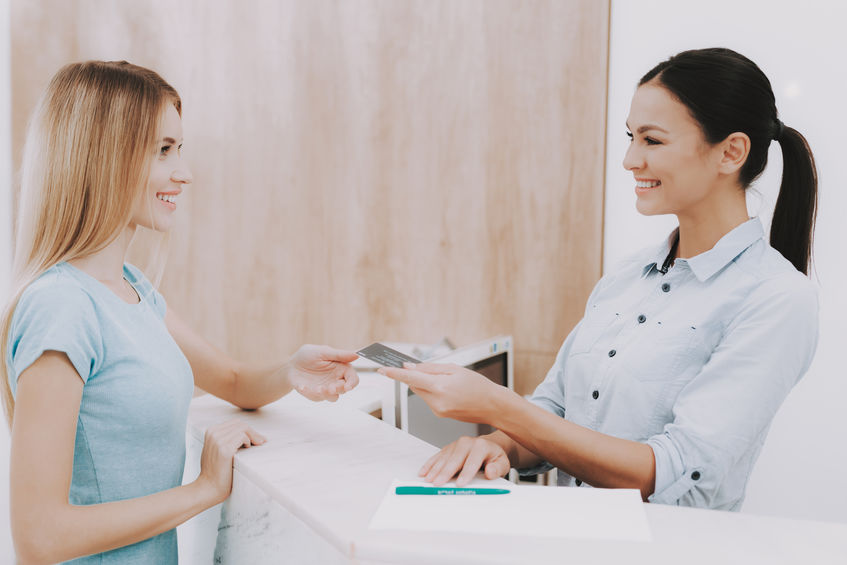 Woman Receptionist. Business Card in Salon. Workplace in Beauty Salon. White Interior. White Reception Desk. Beauty Consept. Smiling Salon Employee. Customer Registration. Employee Talking Client.