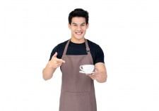 Service minded handsome smiling Asian barista serving coffee studio shot isolated on white background