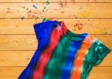 Striped tie dye t-shirt isolated on a classic wooden background. White clothes painted by hand. Flat lay.