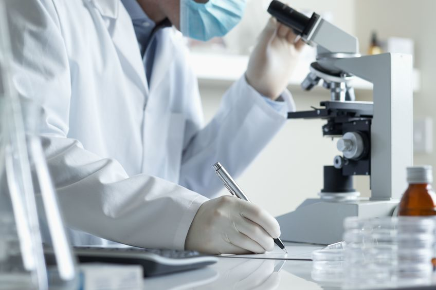 6694883 - scientist conducting research taking notes whilst looking through microscope selective focus