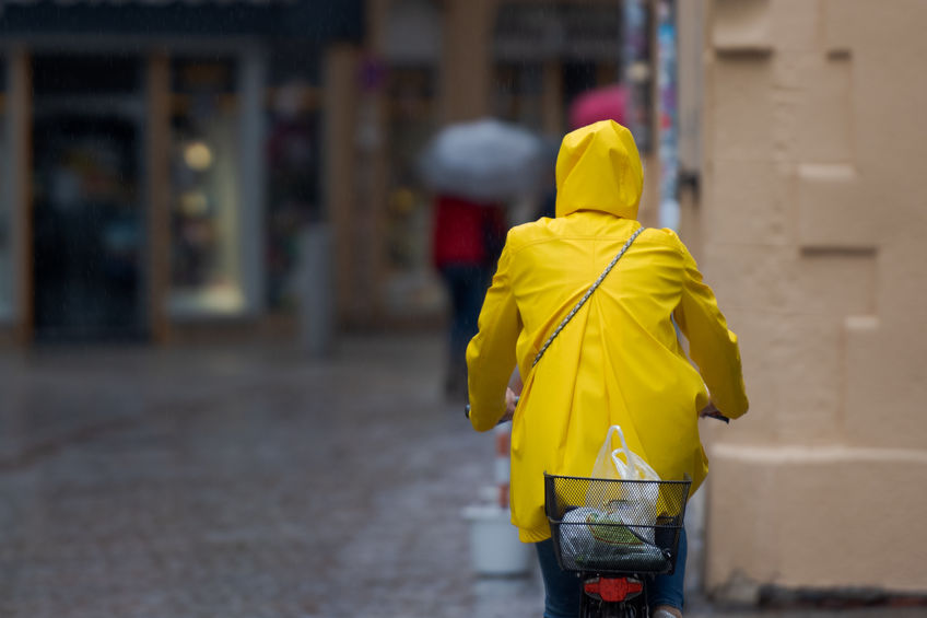 One unrecognizable person with yellow oilskin on bike riding through rainy street in old narrow shooping street with cobblestones on rainy day